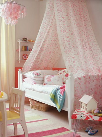 cozy-girl-bedroom-with-high-canopy-draped-over-a-bed